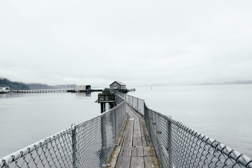 Narrow wooden pier with chain link fence in calm sea near small wooden house against overcast sky in Garibaldi Marina