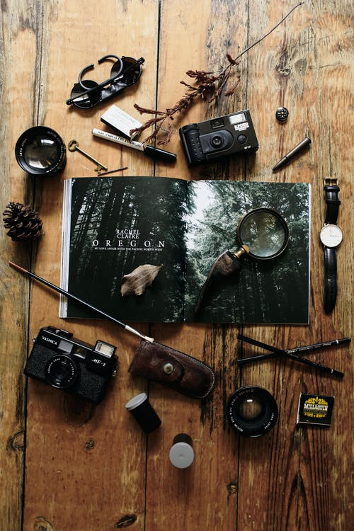 Retro film cameras composed with various traveler accessories on wooden table