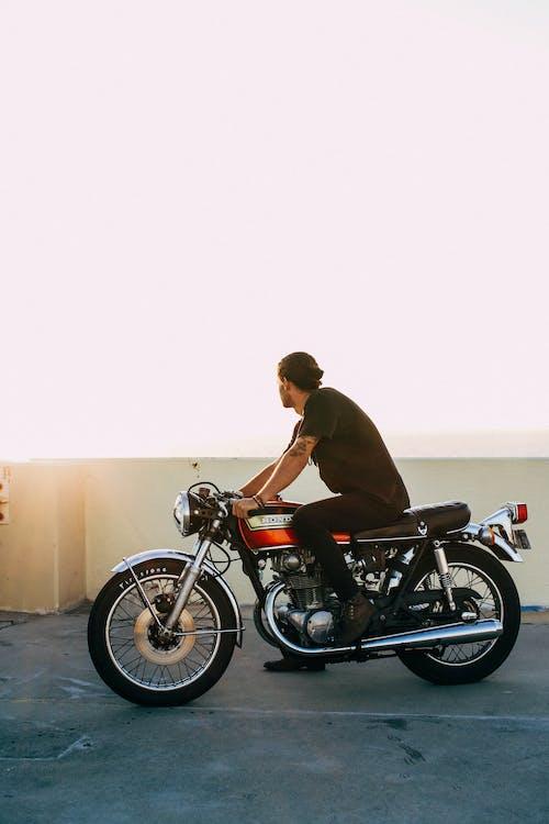 Man in Brown Jacket Riding Black Motorcycle