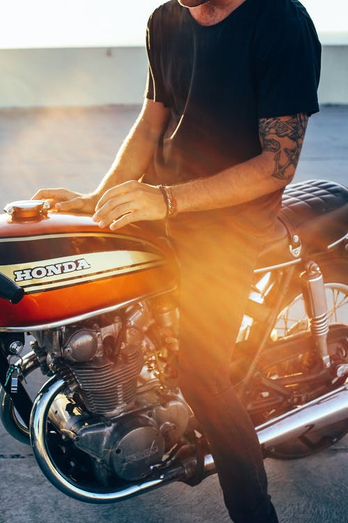 Crop anonymous young tattooed male biker in casual clothes sitting on modern motorcycle on asphalt road on sunny day