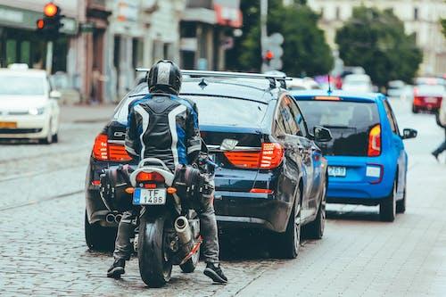 Biker riding motorcycle behind modern cars on crossroad