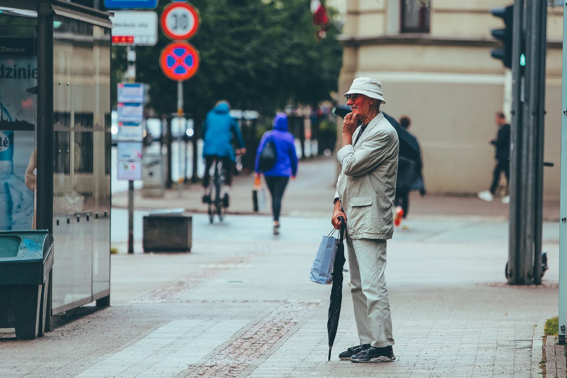 Full body side view of aged male with umbrella standing on pavement and thinking on question