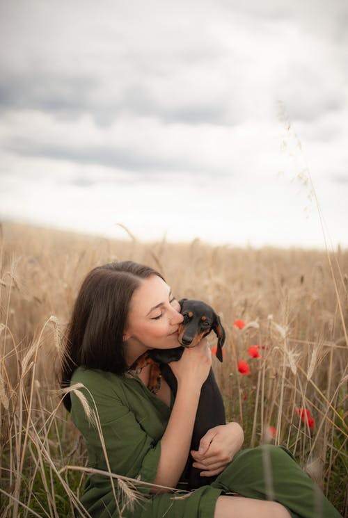 Woman in Green Shirt Carrying Black Short Coated Dog