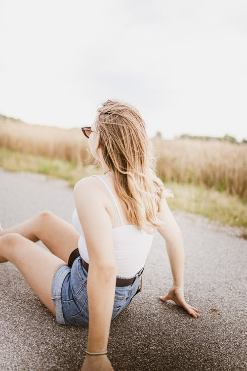 Woman in White Tank Top and Blue Denim Shorts Sitting on Gray Concrete Road