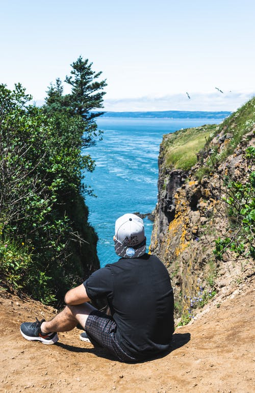 Anonymous male traveler contemplating sea from mount