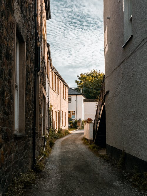 Empty narrow street with aged cobblestone buildings in old town in summer day