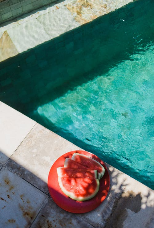 From above of small red slices of watermelon on round plate next to turquoise swimming pool in sunlight