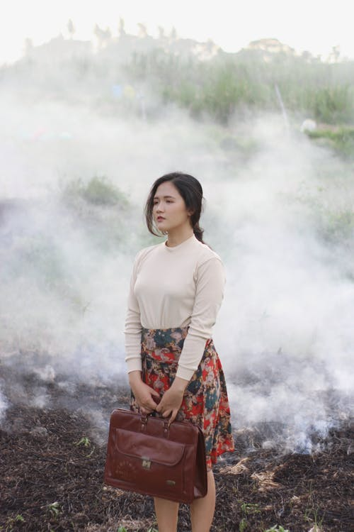 Woman in White Long Sleeve Shirt Standing on Black Soil
