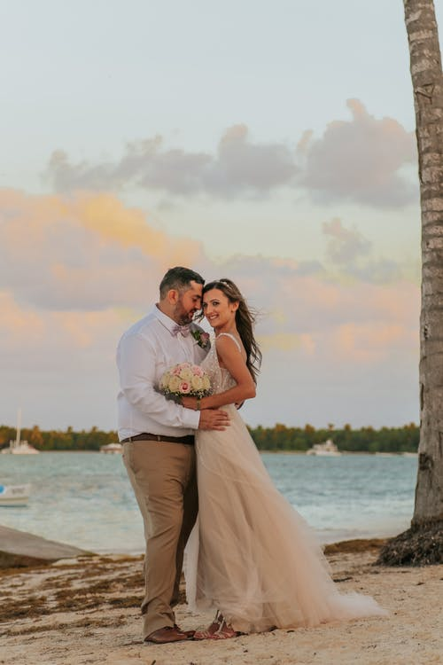 Young glad bearded man embracing smiling stylish bride in wedding dress on sandy lake coast under cloudy sky