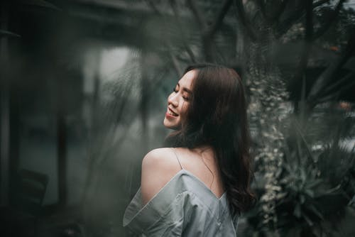 Smiling dreamy Asian woman in trendy clothes near plants