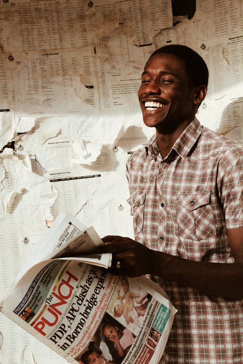 Happy black man with newspaper in hand