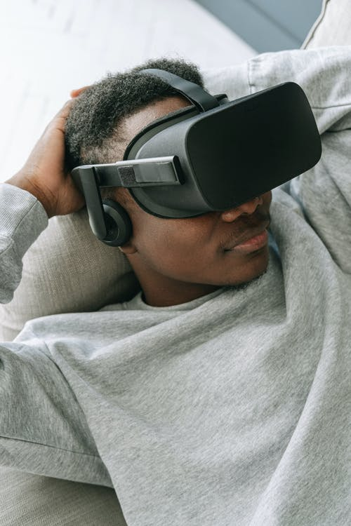 Man in Gray Crew Neck Shirt Wearing Black and Gray Vr Goggles
