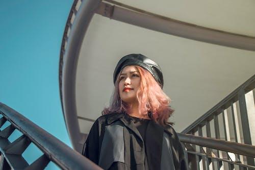 Woman in Black Leather Jacket Standing Near White Metal Railings