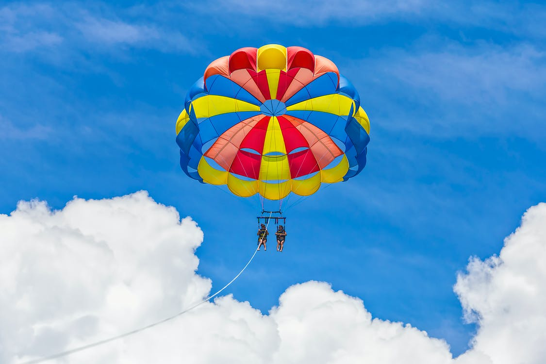 Yellow Red and Blue Parachute in Mid Air Under Blue Sky