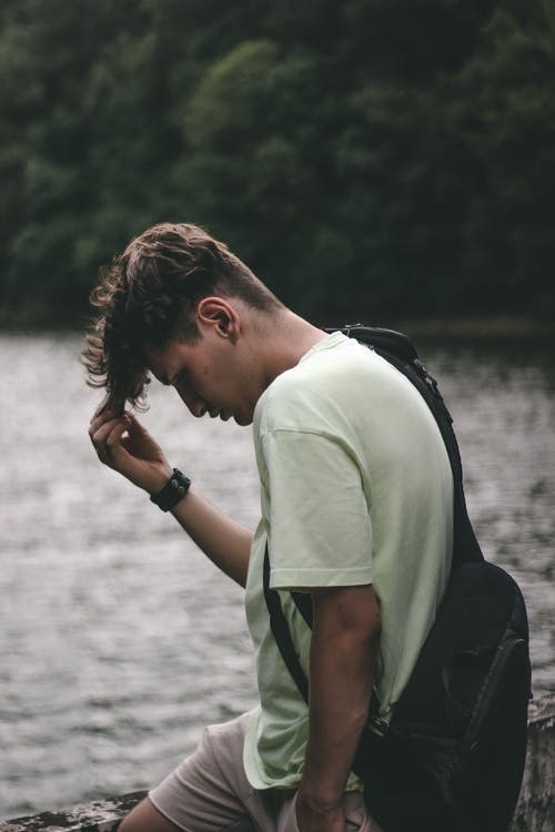 Man in White T-shirt and Black Backpack Standing Near Body of Water