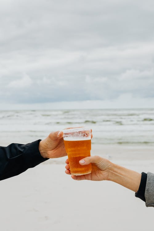 Hands Holding Glass of Beer