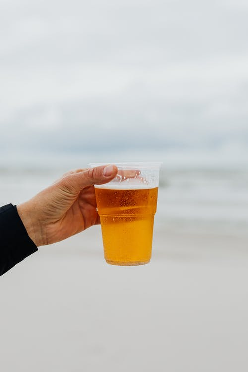Hand Holding Glass of Beer on the Beach