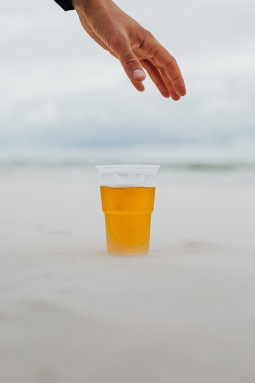 Hand Reaching for a Glass of Beer