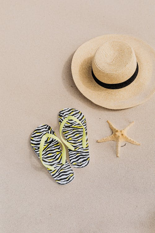 Beach Hat Flip Flops and a Starfish on the Sand