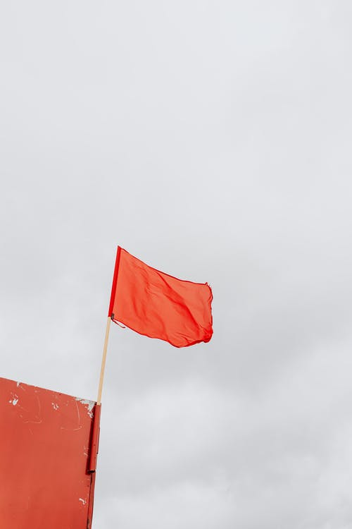 Red Flag on Pole Under White Sky