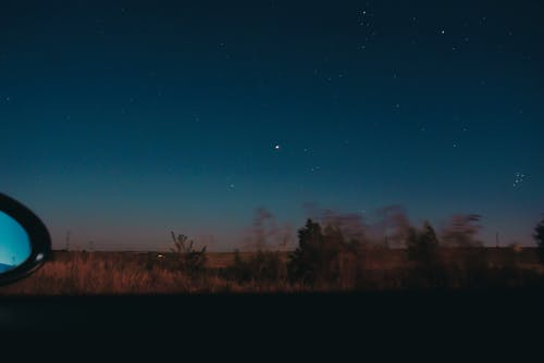 View through moving car window of horizon line with dark star sky and blurred trees