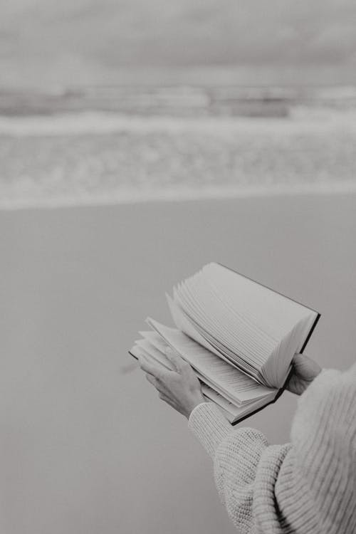 Black and White Photo of Person Holding a Book