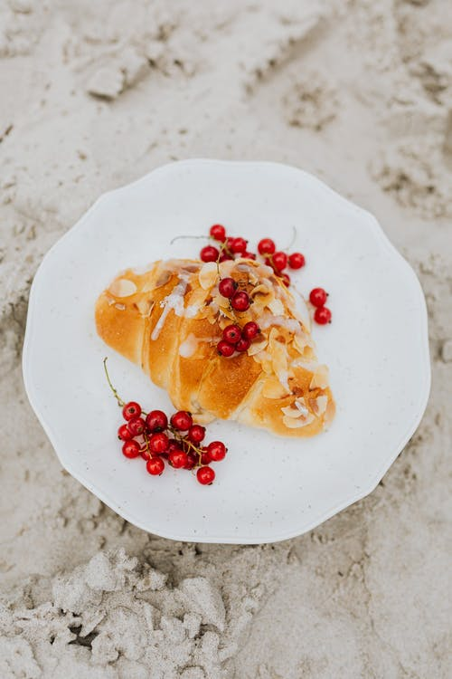 Croissant and Currants on White Ceramic Plate