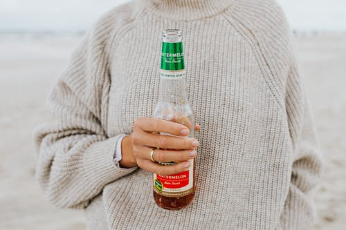 Woman in Sweater Holding a Beer Bottle