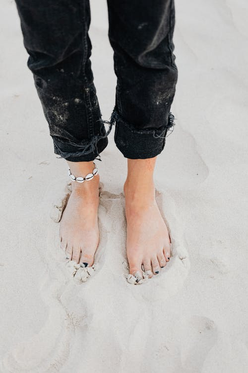 Person Standing on Brown Sand