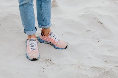 Close-Up Photo of a Person's Feet Wearing Orange and Blue Shoes on the Sand