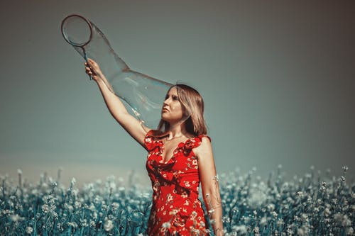 Calm woman with soap bubbles in meadow