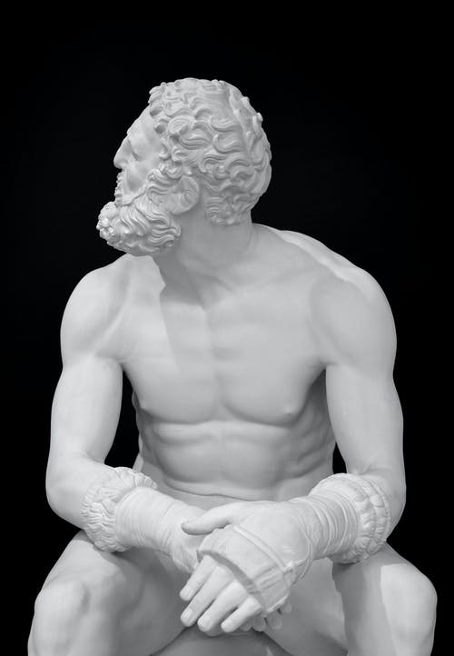 White Concrete Statue of a Topless Man