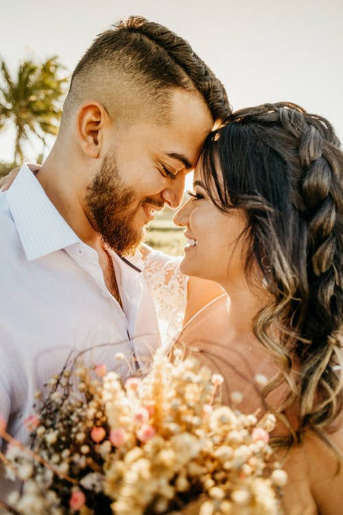 Side view of romantic young ethnic groom and bride touching foreheads and hugging each other while standing on beach with flowers in hand during wedding celebration