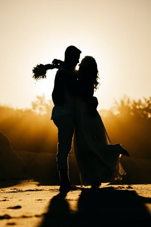 Side view silhouettes of happy young couple hugging each other while relaxing on sandy beach during date at sunset