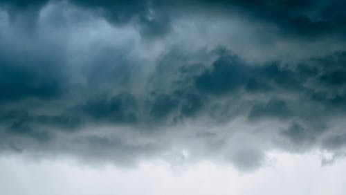 Fluffy dark rainy clouds floating in dramatic gray sky in stormy rainy weather