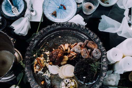 Top view of assorted delicious dried with cheese fruits on tray served on table near dishware and candles during festive dinner