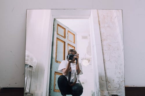 Photographer with photo camera taking selfie in mirror