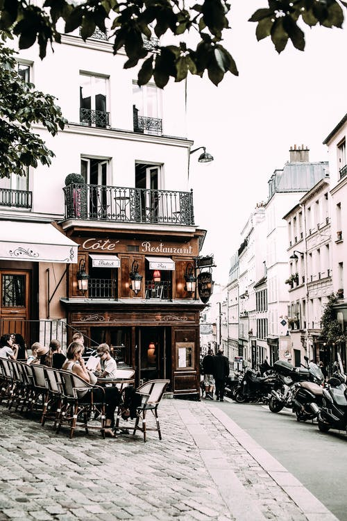 People sitting at tables in street cafe
