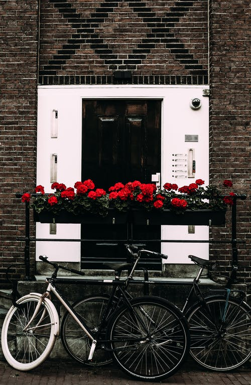 Bicycles and flowers near entrance of brick building