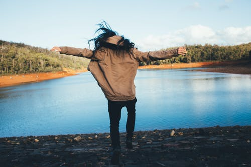 Faceless person in outerwear jumping happily on lake shore