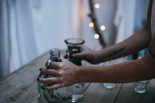 Crop anonymous female putting glass vases on wooden table in creative construction made of hanging white bedsheets and decorated with garlands at twilight