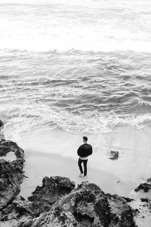 Unrecognizable man standing on waving seashore