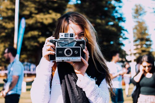 Young female photographer in casual outfit taking pictures on retro photo camera while standing in crowded sunny park