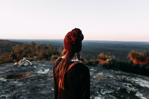 Anonymous female traveler on hill admiring valley with forest