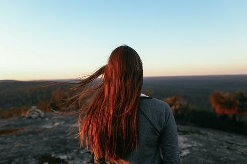 Back view of unrecognizable female traveler with red hair wearing warm clothes while standing on hill and admiring valley with trees under bright cloudless sky in sunny day