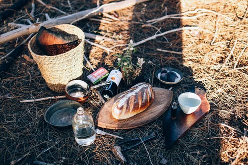 Bread and utensil near bottles and basket on grass