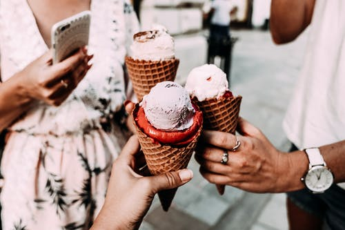 Crop anonymous friends in casual summer clothes clinking delicious cone ice creams while gathering on street