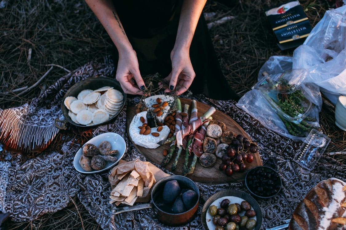 From above crop anonymous female serving yummy food including asparagus with bacon potatoes and grapes on wooden board placed on plaid during picnic in nature