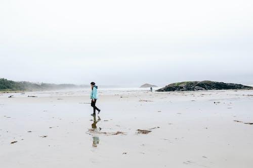 Unrecognizable person in outerwear walking on wet misty seashore