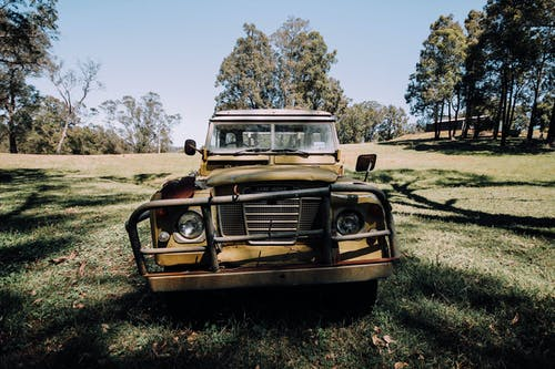Grunge abandoned car left on grassy meadow